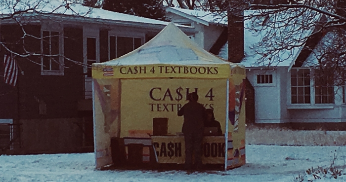 outdoor cash for textbooks station in snow with two people