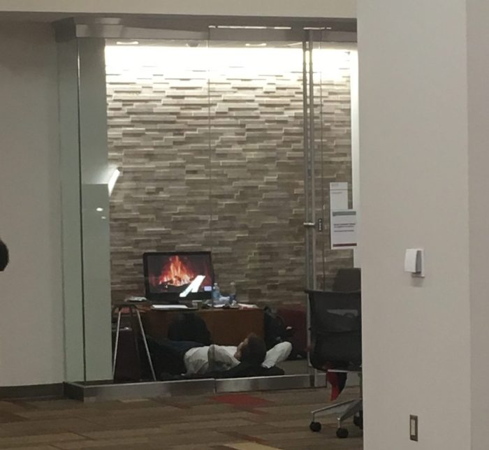 student lying on the ground watching a screen with fireplace on it in group study room